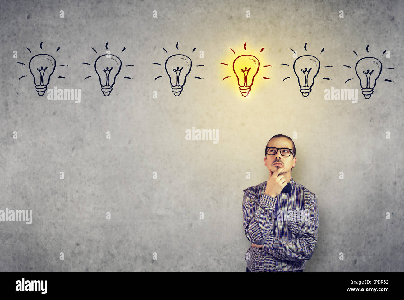 Young pensive man in eyeglasses looking up having brilliant idea. - Stock Image
