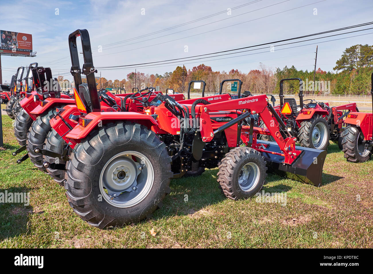 Rows of new Mahindra red tractors and farm equipment for sale at a Mahindra tractor dealership, some with optional - Stock Image