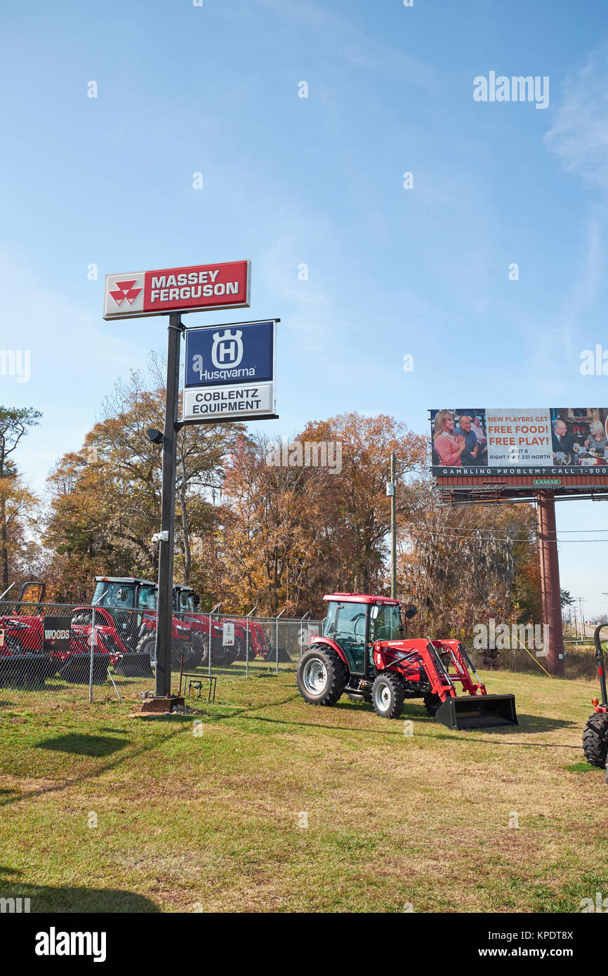 New Mahindra 2500 series shuttle cab tractor on display beneath signs for Massey Ferguson, Husqvarna, and Coblentz - Stock Image