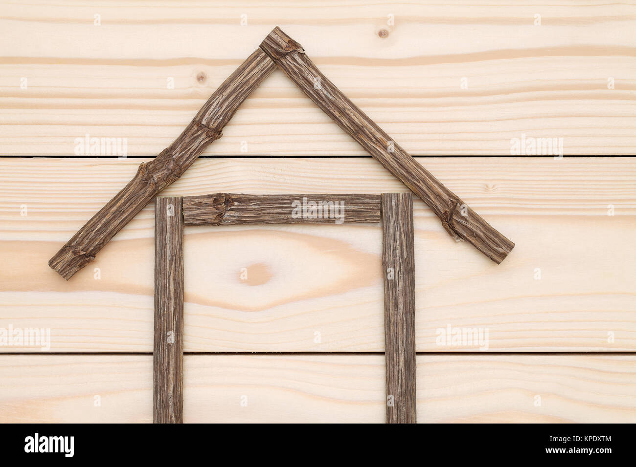 small house made of branches on wood background Stock Photo