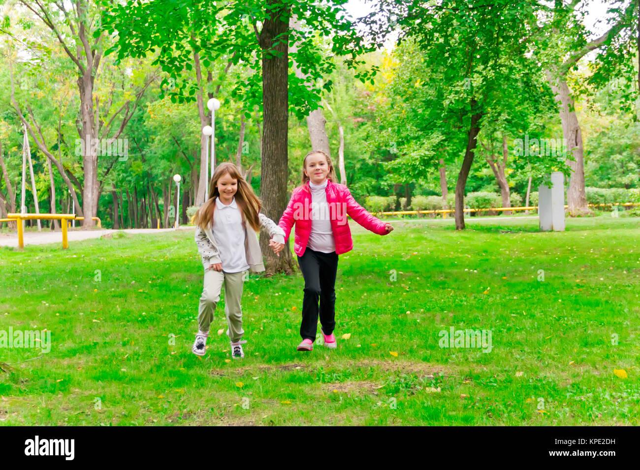 Cute two running girls - Stock Image