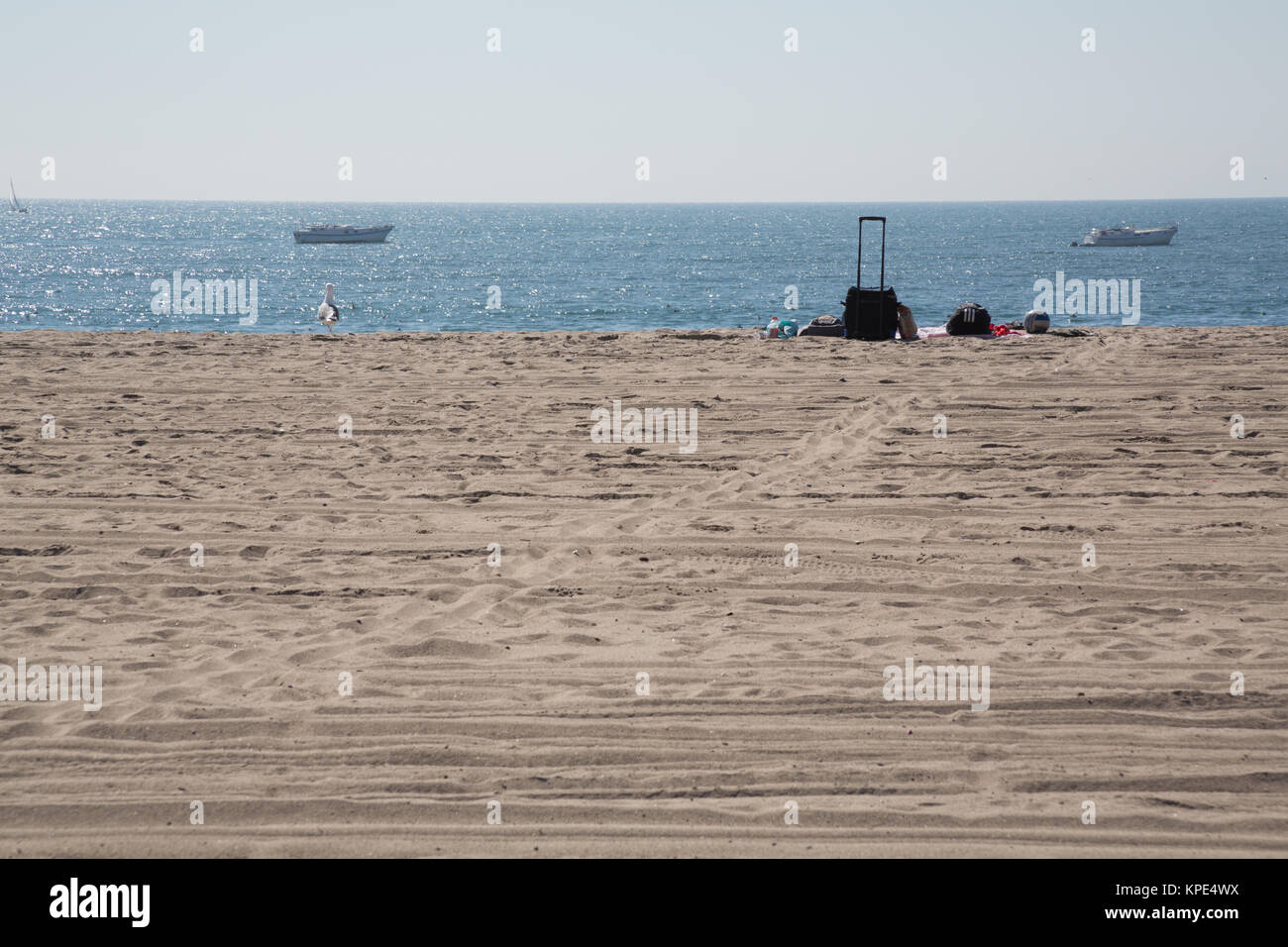 A rolling cooler,  a picnic blanket and volleyball  on the sand and boats in the water at Dockweiler State Beach, - Stock Image