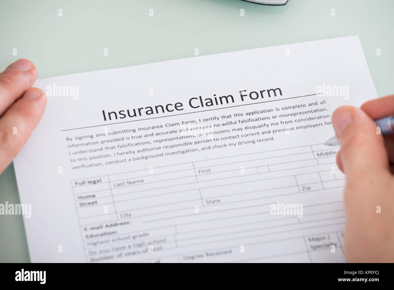 Person Hand Over Insurance Claim Form - Stock Image
