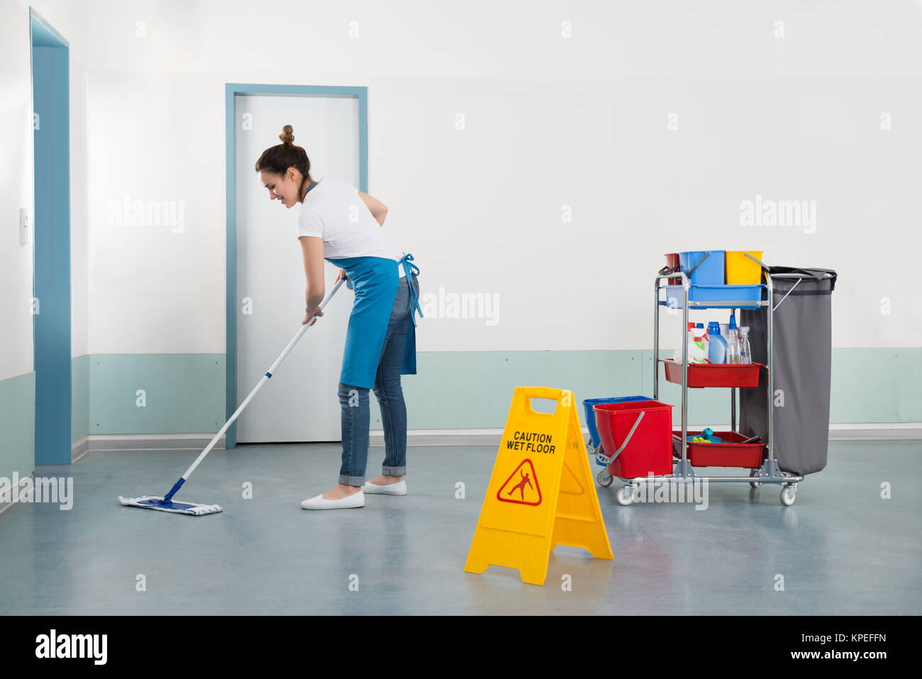 Female Janitor Mopping Corridor - Stock Image