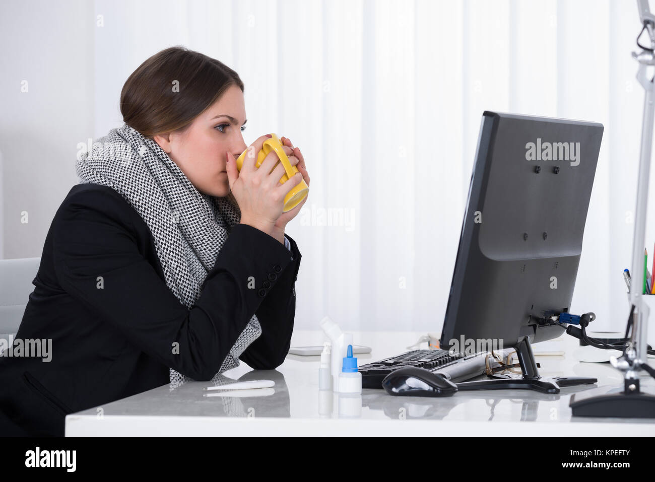 Businesswoman Drinking With Mug At Desk - Stock Image