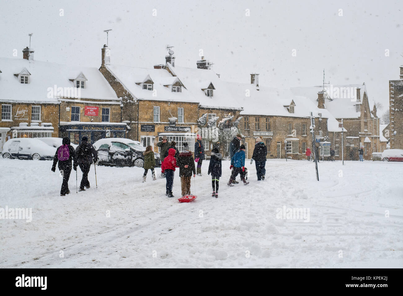 People walking through the market place at christmas time in the snow. Stow on the Wold, Cotswolds, Gloucestershire, - Stock Image