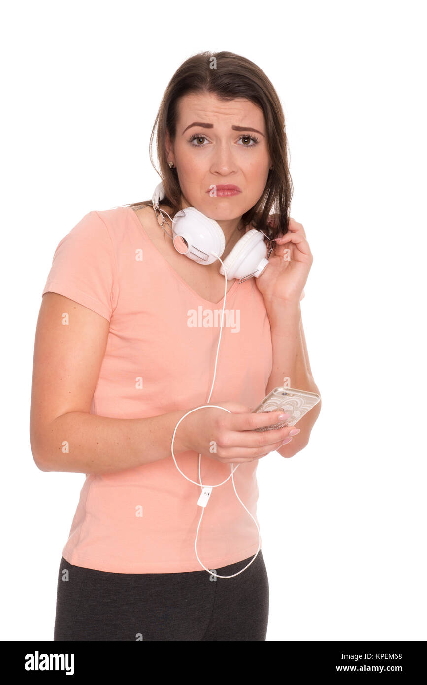 young woman with headphones and mobile phone looks skeptical - Stock Image