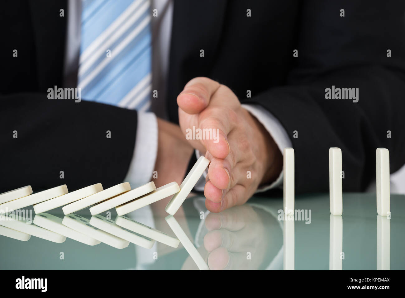 Businessperson Stopping Dominos Falling On Desk - Stock Image
