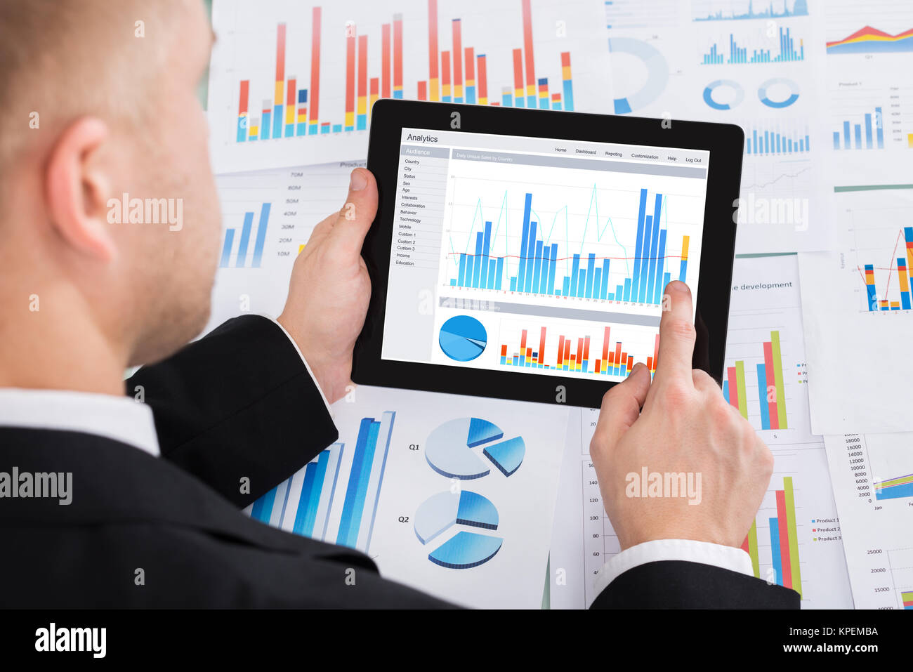 Businessperson Analyzing Graph On Digital Tablet - Stock Image