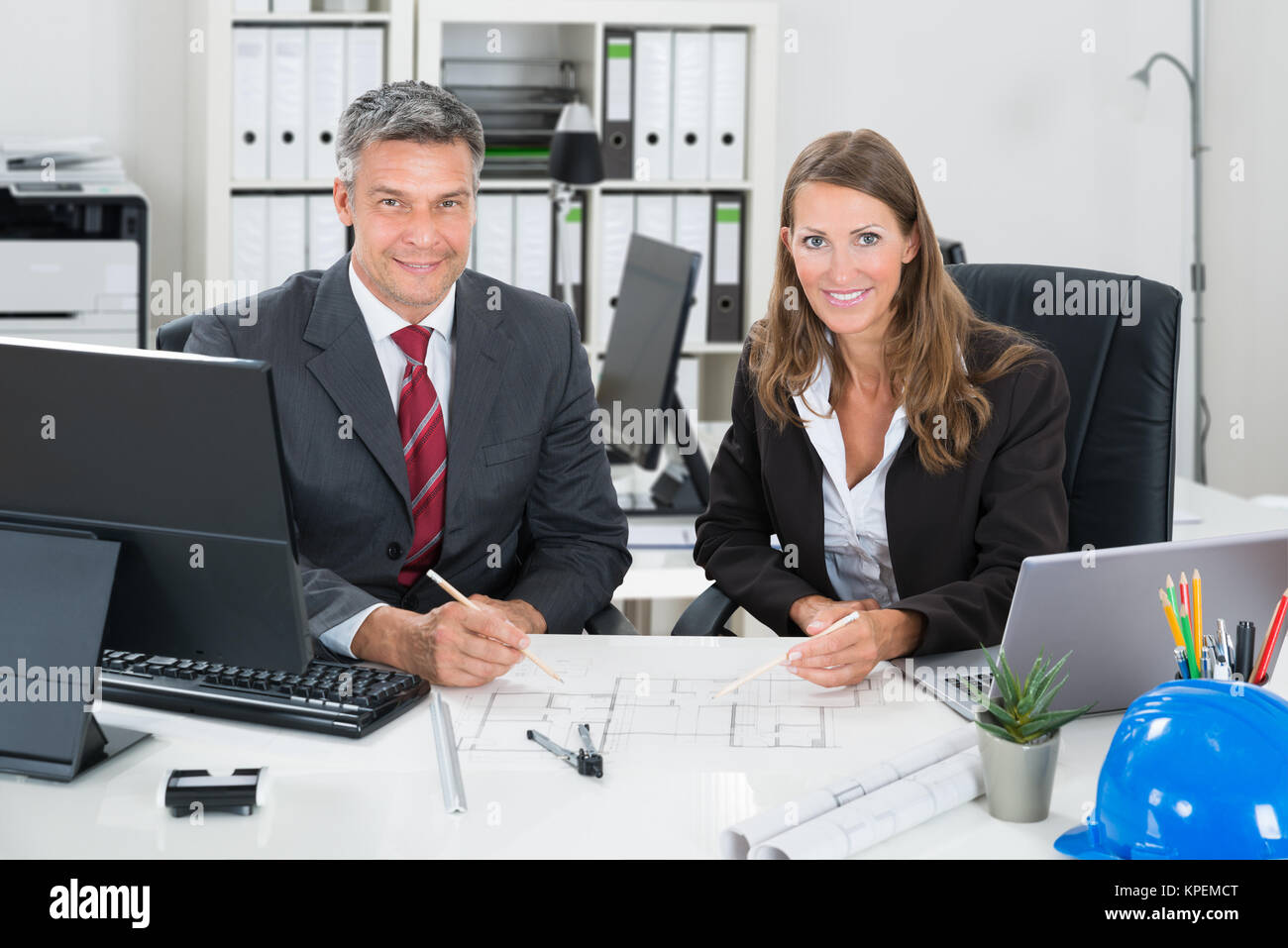 Architects Working On Blueprint At Desk - Stock Image