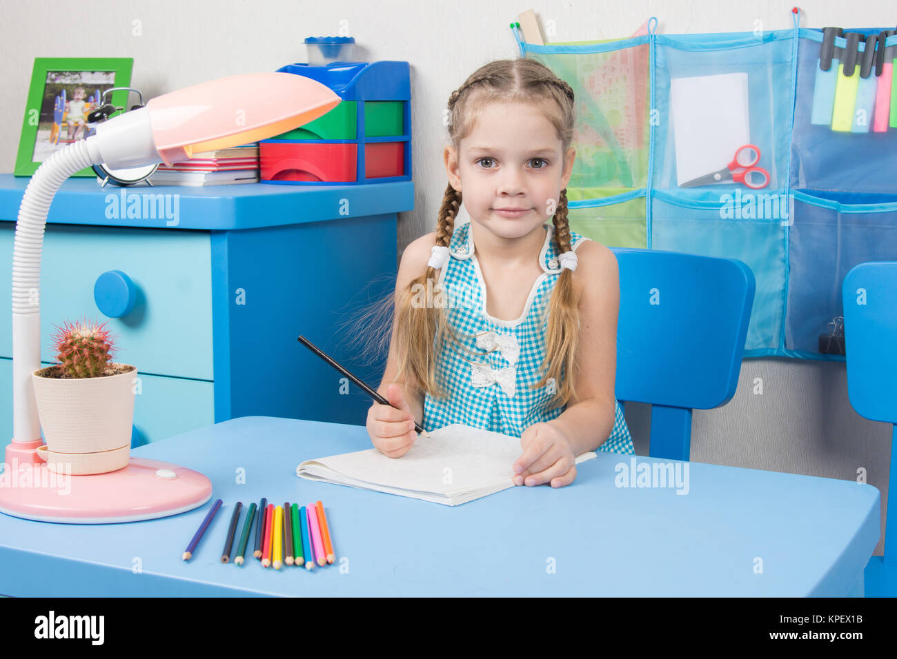 Five-year girl draws pencil in a notebook and looked into the frame - Stock Image