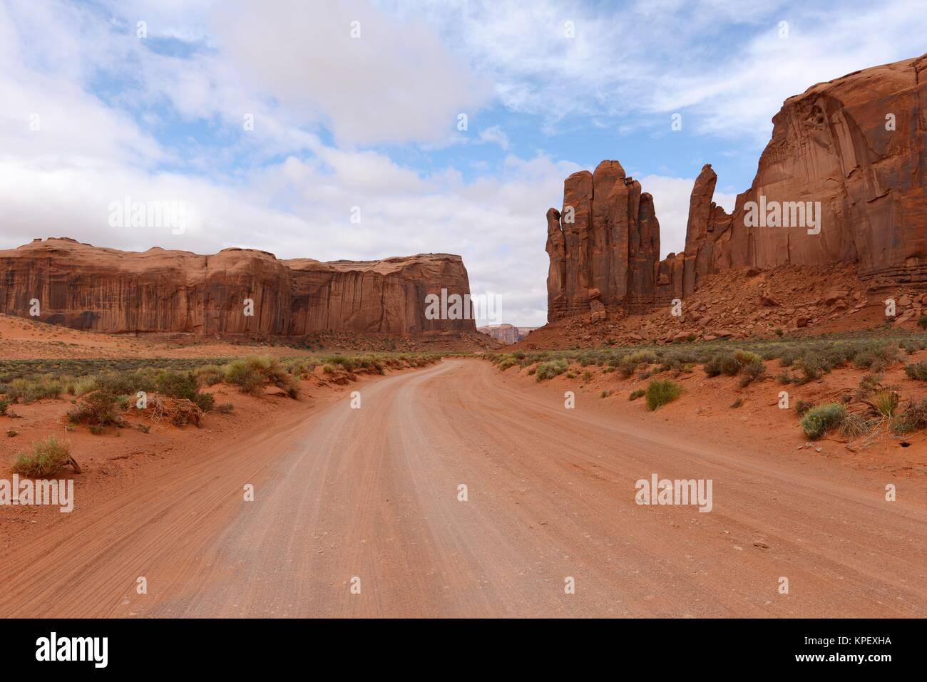 Red Desert Valley Road - A unpaved dirt road winding through red sandstone desert valley in the famous Monument - Stock Image