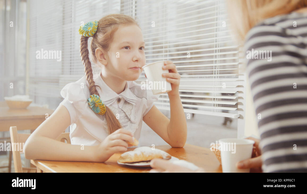 Little girl with mommy in cafe - teen explains something for mother - Stock Image