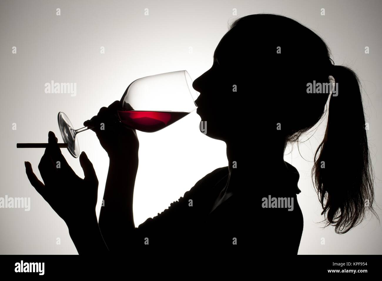 female drinking red wine while smoking - Stock Image