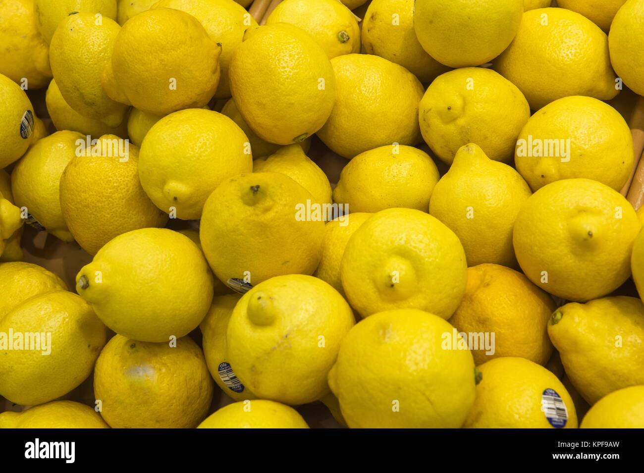 fresh lemons from market display shelves real with flaws and bru - Stock Image