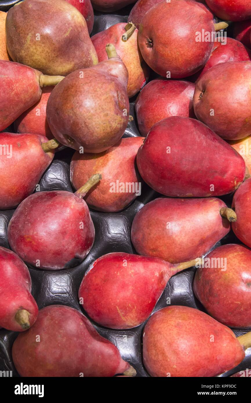 fresh red pears from market shelves real with flaws and bruises - Stock Image