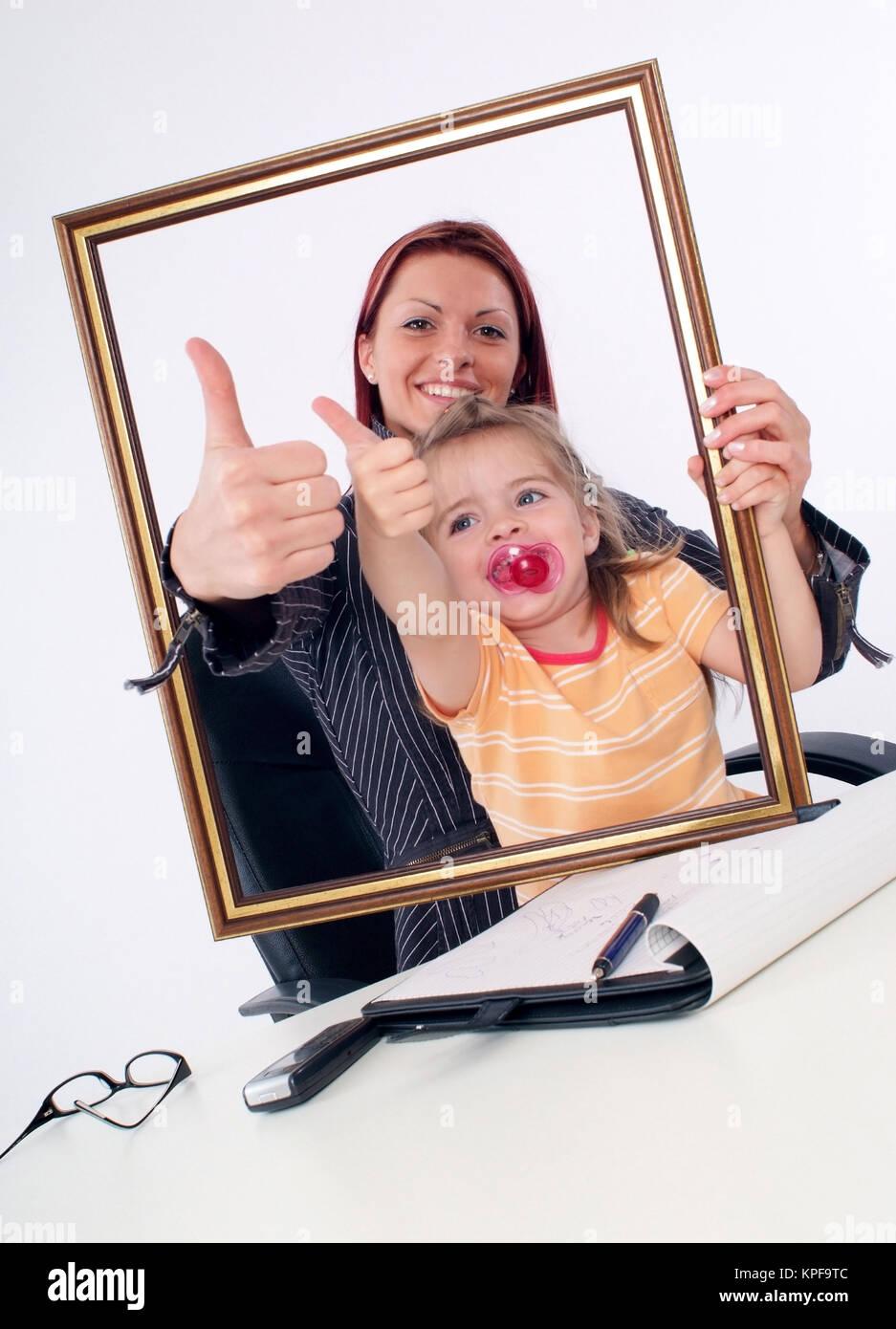 Symbolbild Karrierefrau und Mutter, erfolgreiche Geschaeftsfrau mit Tochter am Schreibtisch - sucessful businesswoman Stock Photo