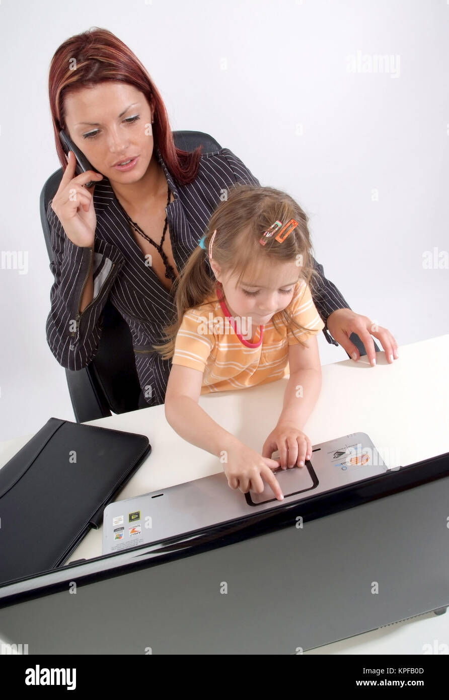 Geschaeftsfrau mit Kind arbeitet am Laptop - business woman with child using laptop - Stock Image