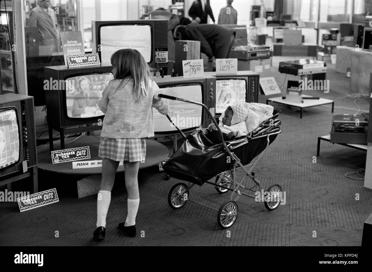 Ethnic diversity 1970s Uk, black African baby in pram being pushed around department store by white older sister - Stock Image