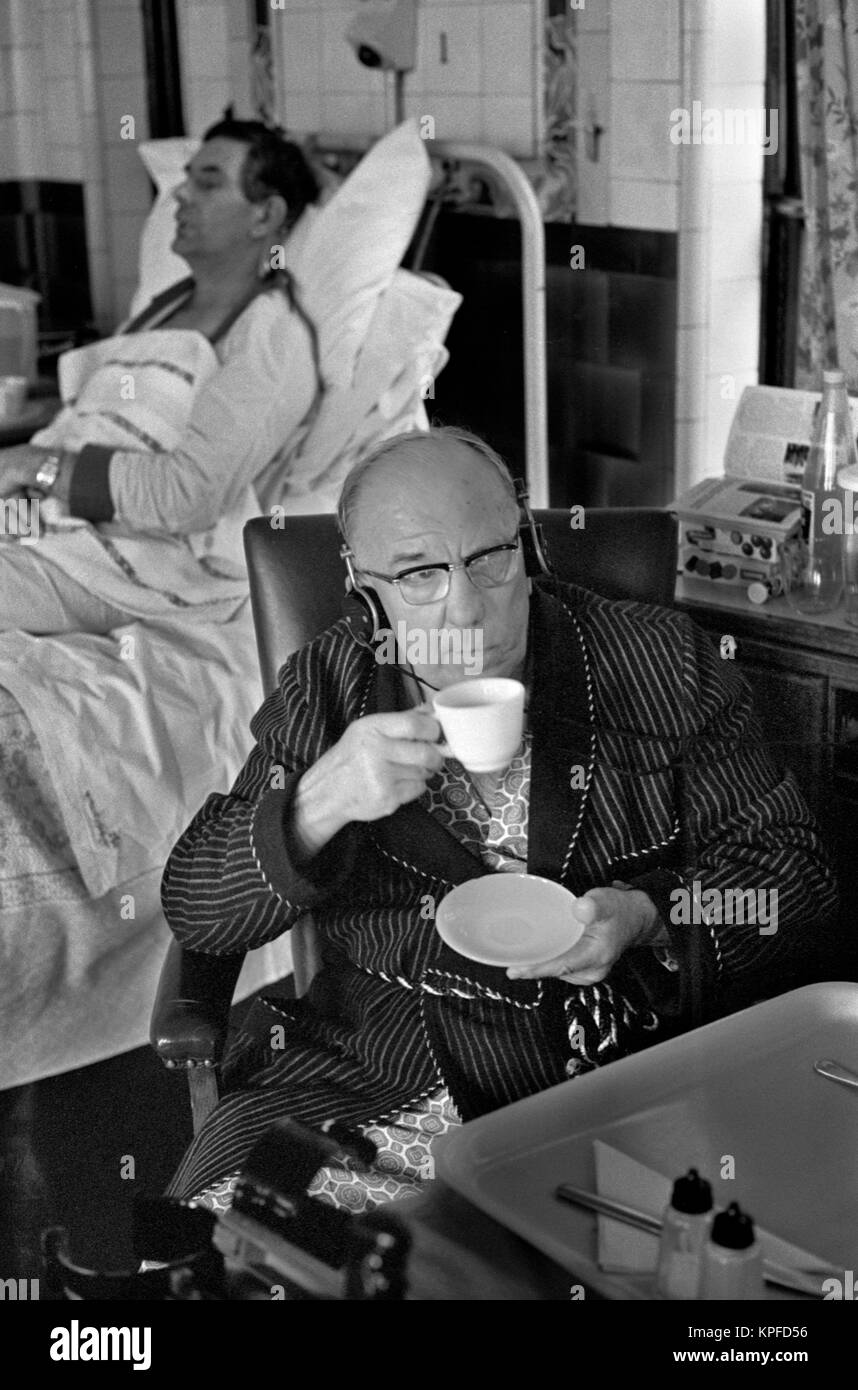 Charing Cross Hospital London 1970S NHS  elderly man patient listening to television on headphones, there are several - Stock Image