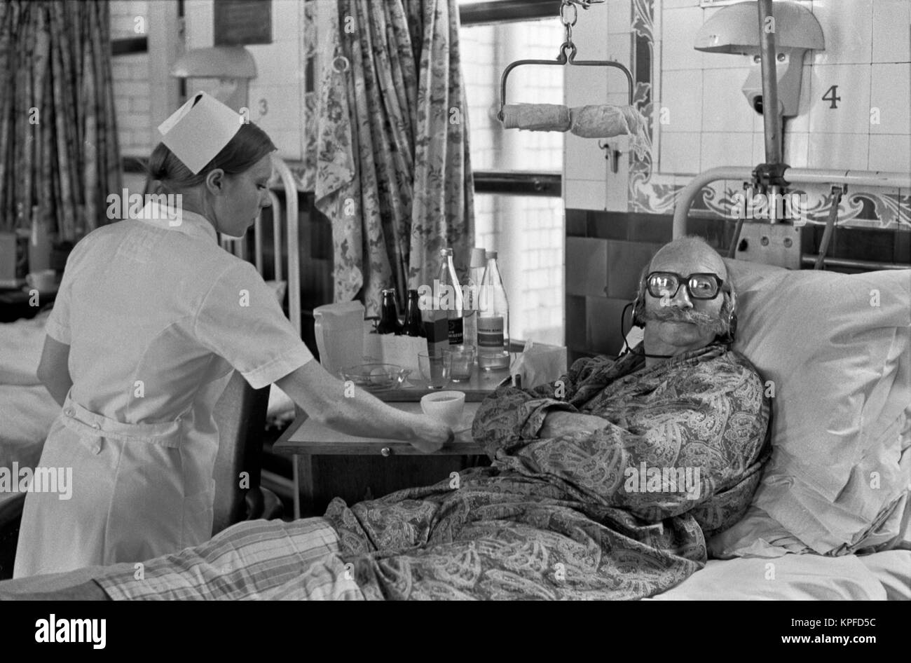 1970S NHS  Charing Cross Hospital London nurse giving patient a cup of tea. Listening and watching Tv with head - Stock Image