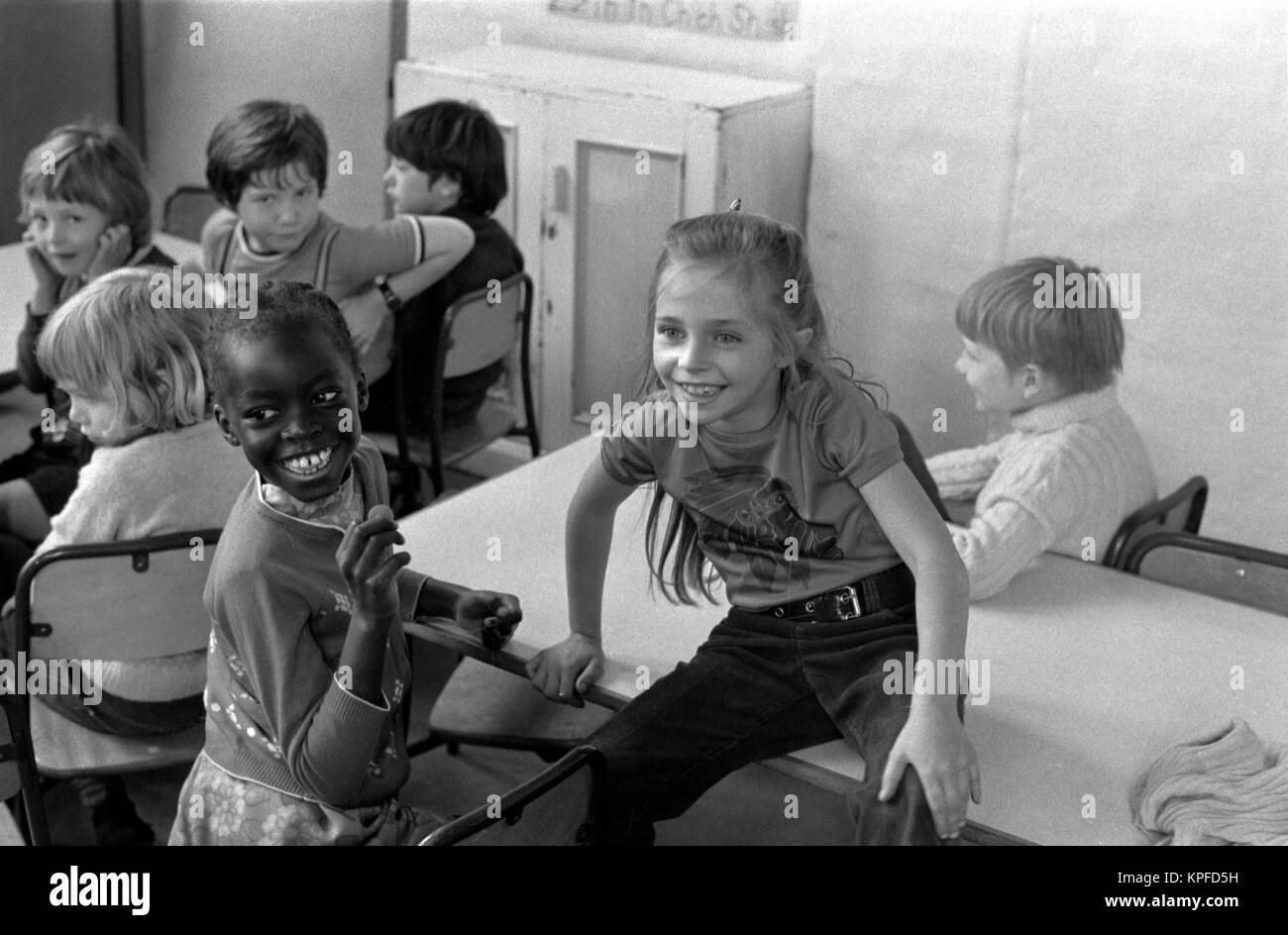 Primary school children 1970s Black African child with white school friend smiling, happy, London 70s. Uk HOMER - Stock Image
