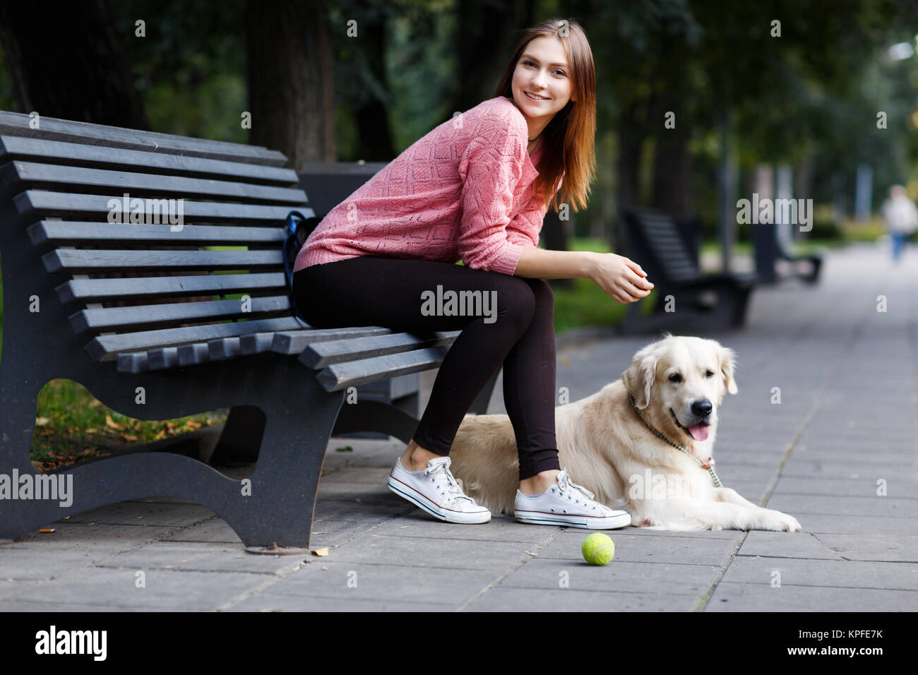 Photo of smiling girl sitting on bench, dog retriever - Stock Image