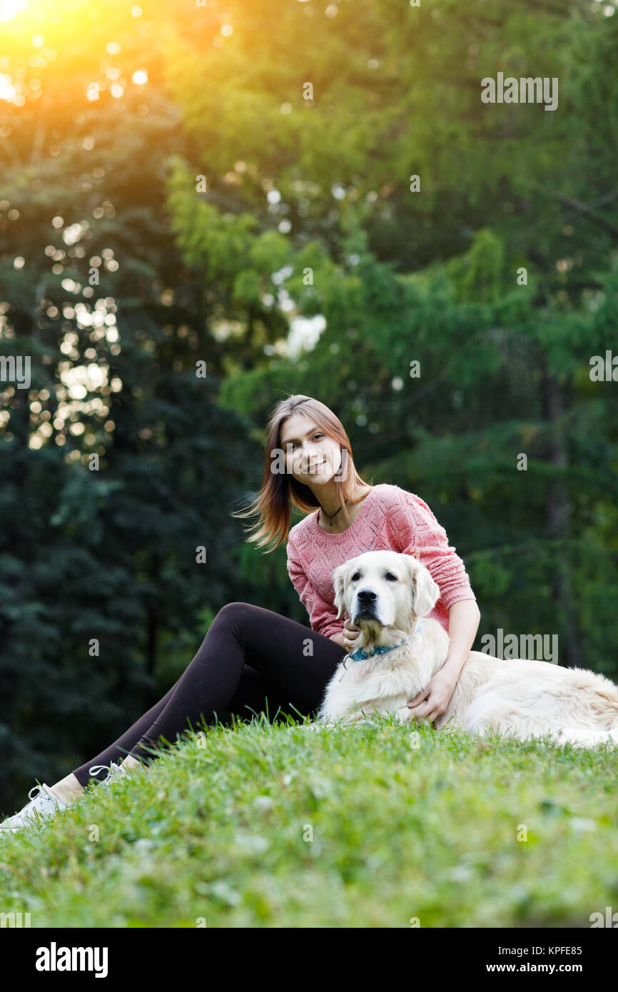 Image from below of woman sitting with dog on green lawn - Stock Image