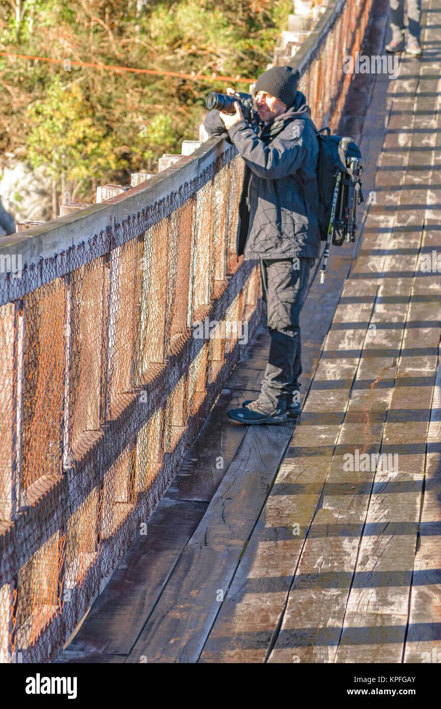 AYSEN, CHILE, APRIL - 2017 - Man taking photos at bridge, queulat national park, Aysen, Chile - Stock Image