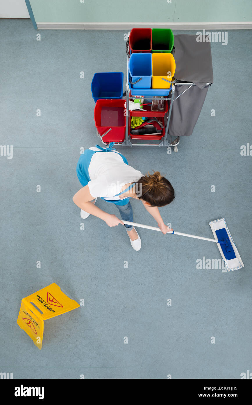 Female Janitor Mopping Floor - Stock Image