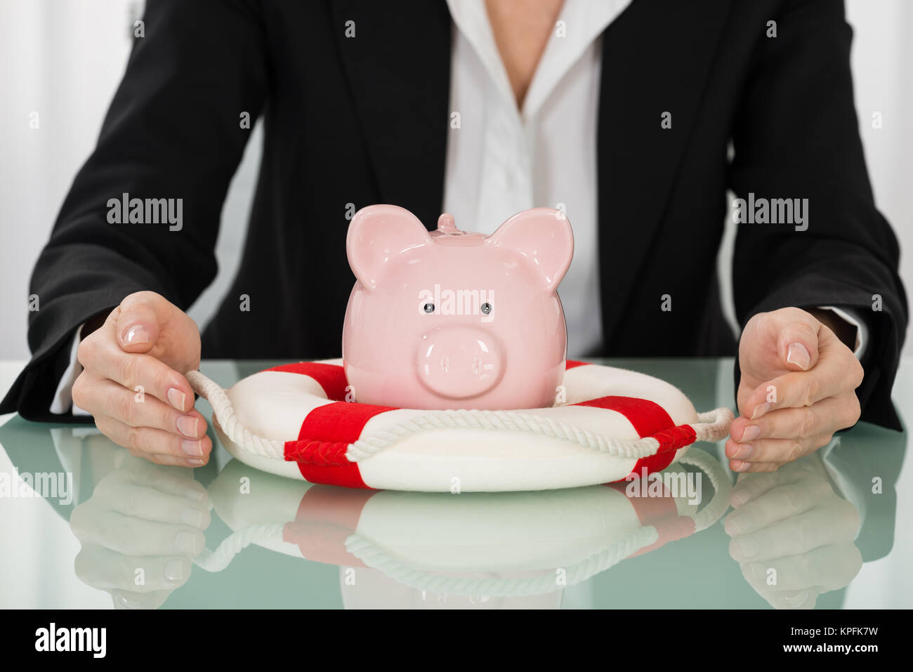 Businesswoman Hand Protecting Piggybank With Lifebelt - Stock Image