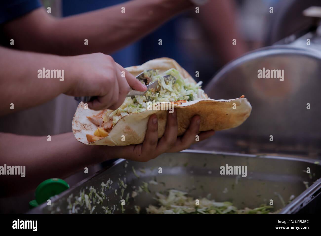 Man cutting and preparing doner kebab - Stock Image
