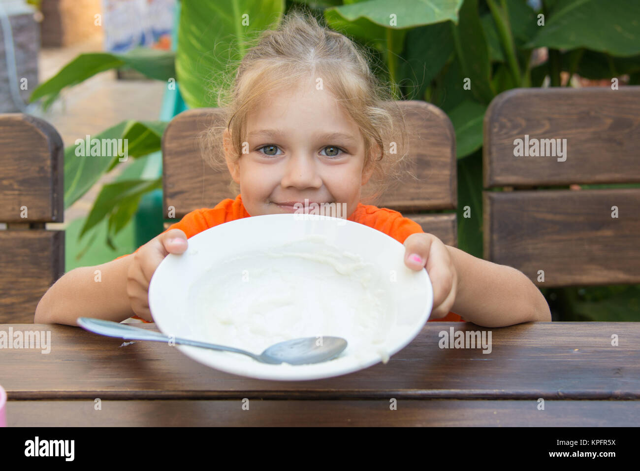 Five-year girl showing empty plate to eat Stock Photo