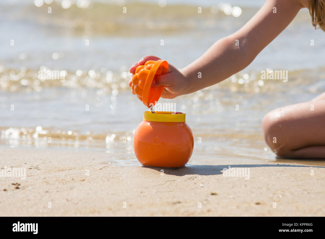 Child sprinkles wet sand from the molds in a pot on the sandy beach seashore - Stock Image