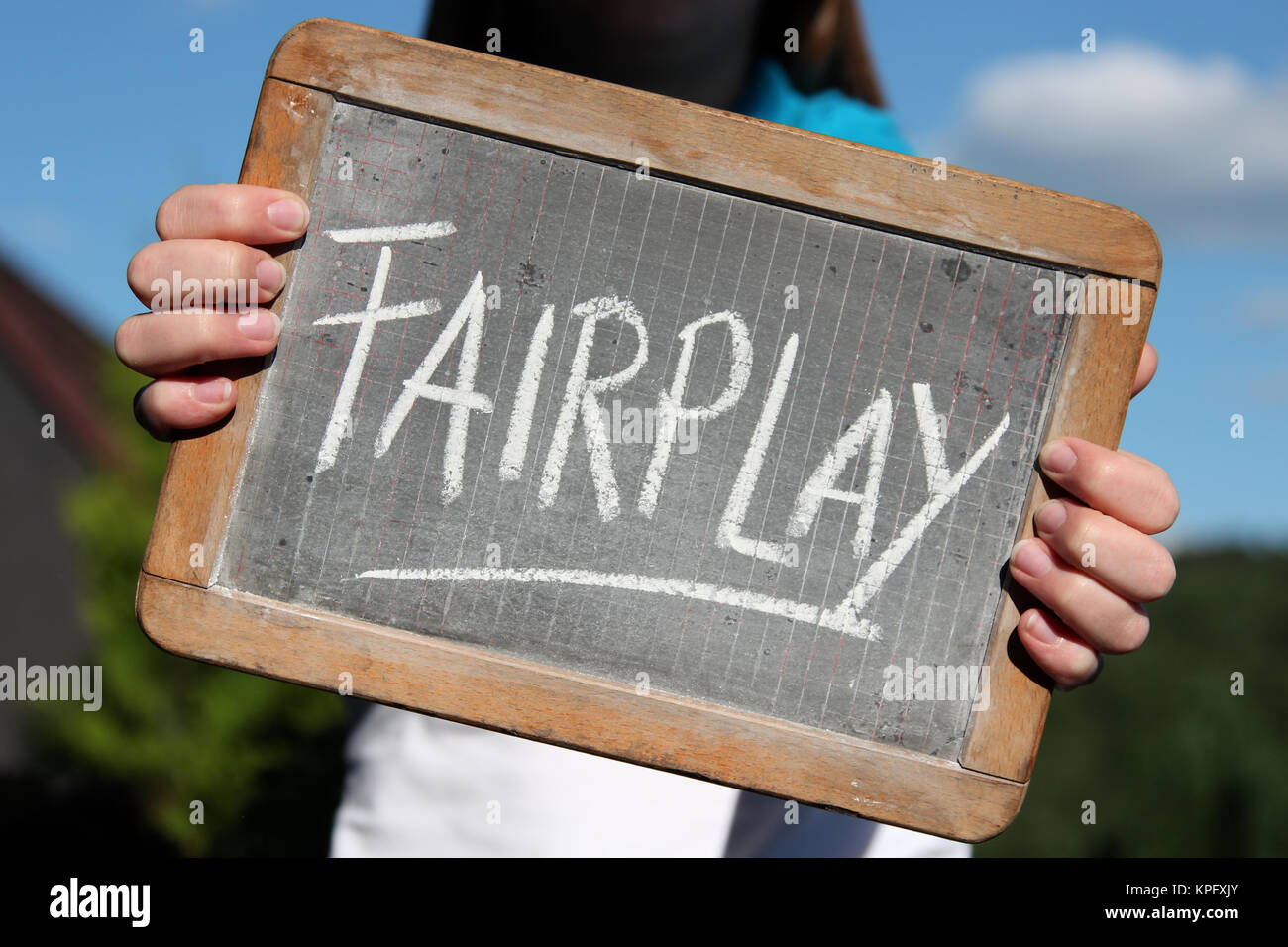 FAIRPLAY written with chalk on slate shown by young female - Stock Image