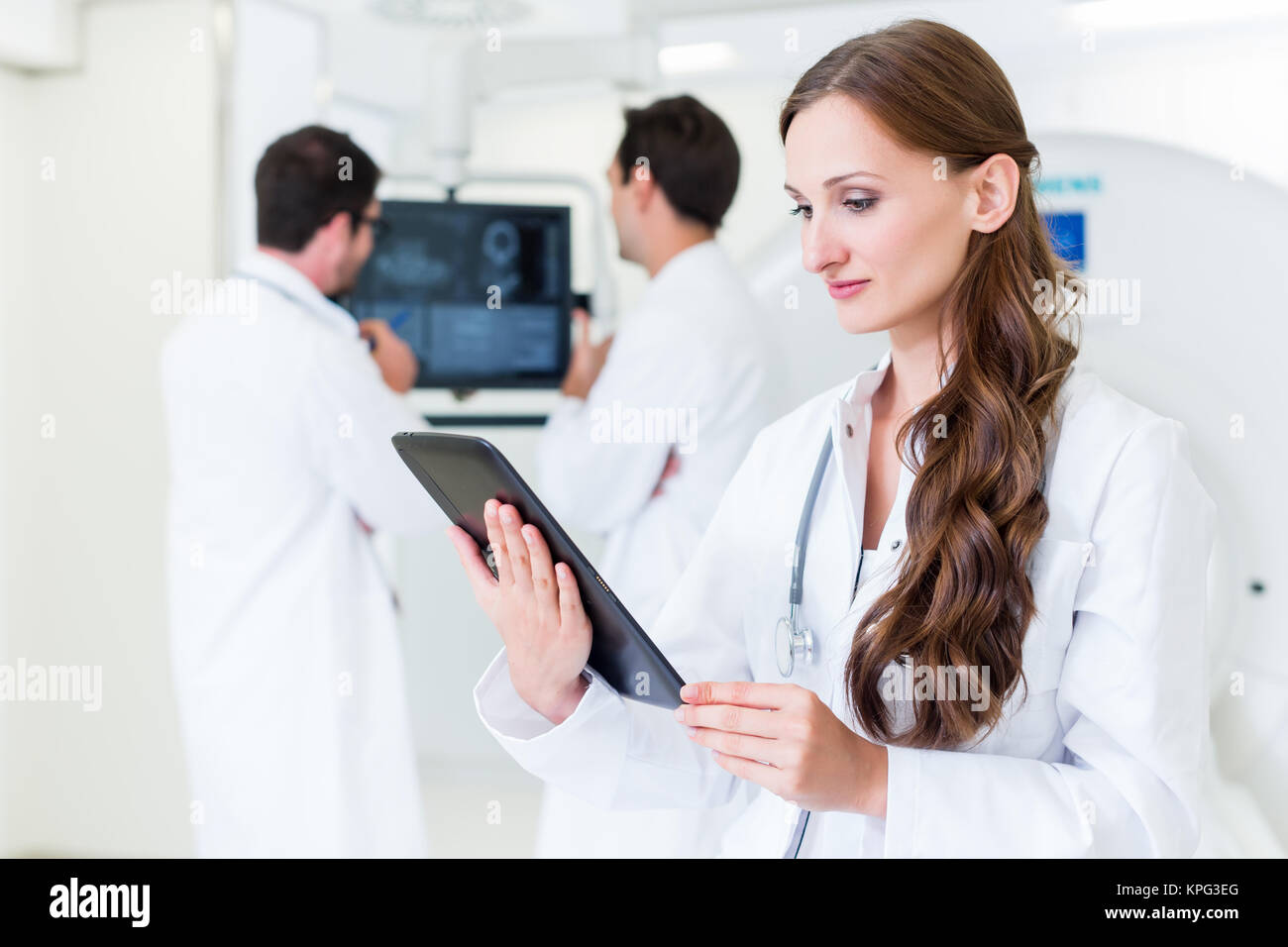 female doctor with colleagues in hospital at ct device - Stock Image