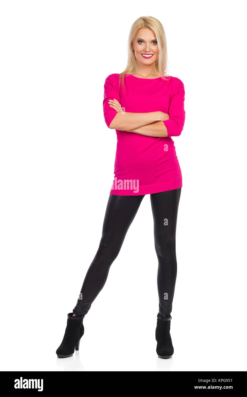 Smiling beautiful blond woman in black leggings, high heels and pink sweater is standing with arms crossed and looking - Stock Image