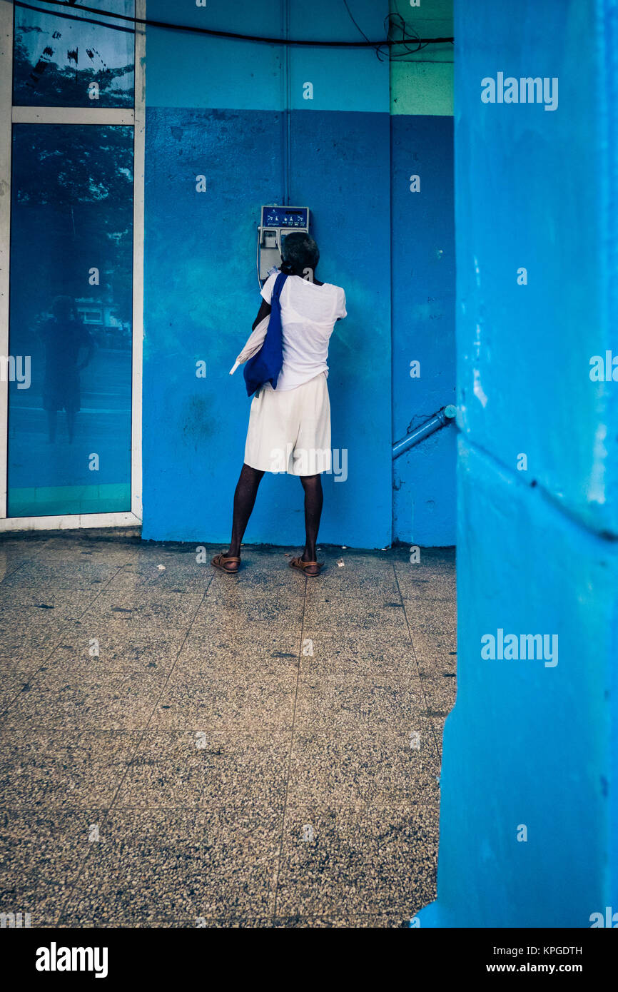 Afro Caribbean female makes call from public payphone, Havana Cuba - Stock Image
