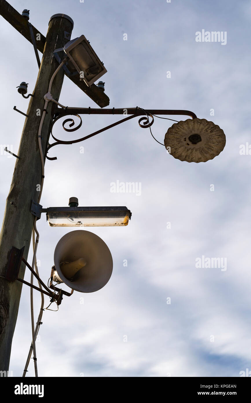 An old power pole with three different types of lighting still on the pole Stock Photo