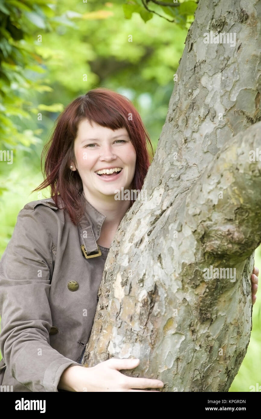 Model released , Froehliche Frau, 25+, umgreift einen Baumstamm - lucky woman next to a tree - Stock Image