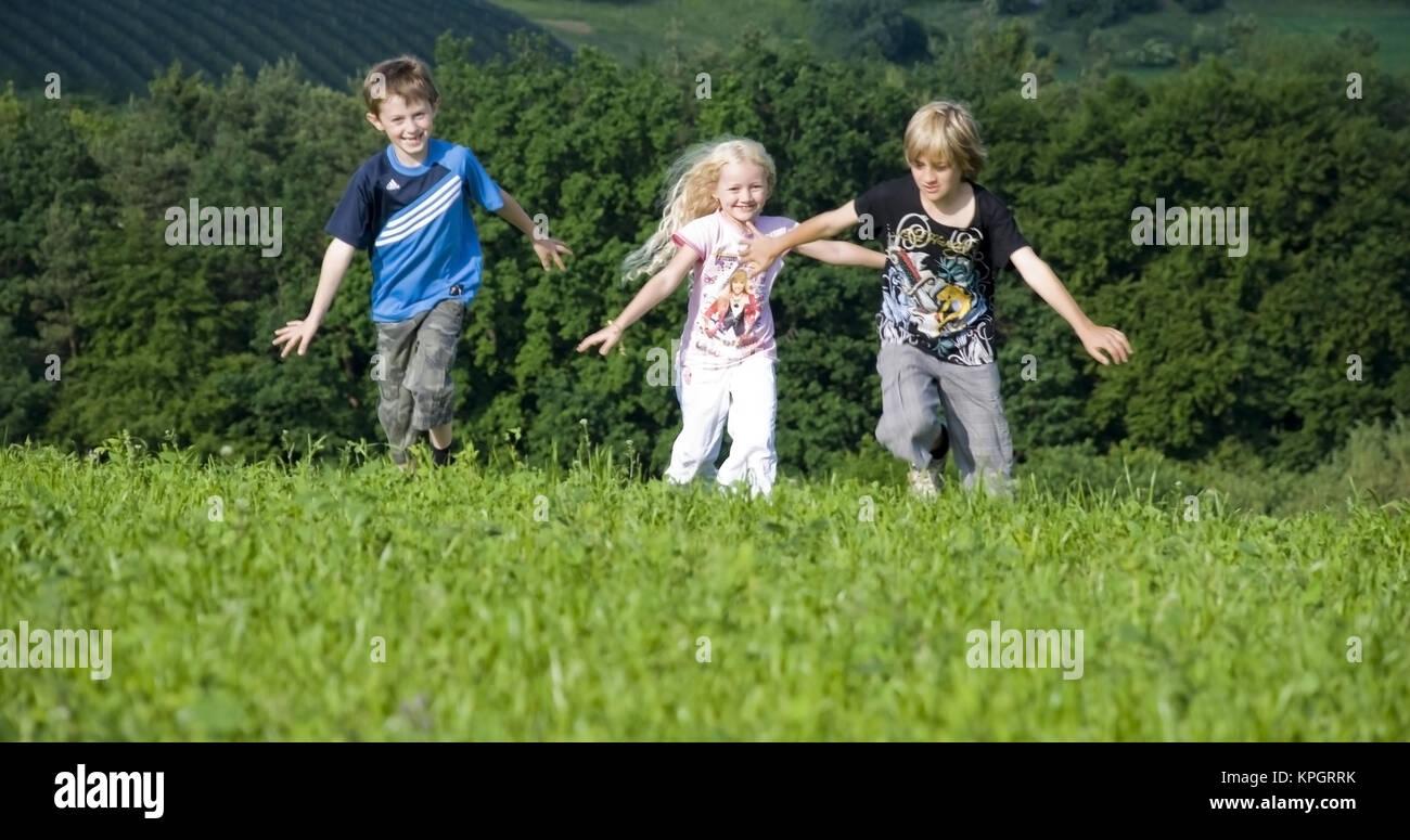 Kinder laufen in der Wiese - kids running in meadow - Stock Image