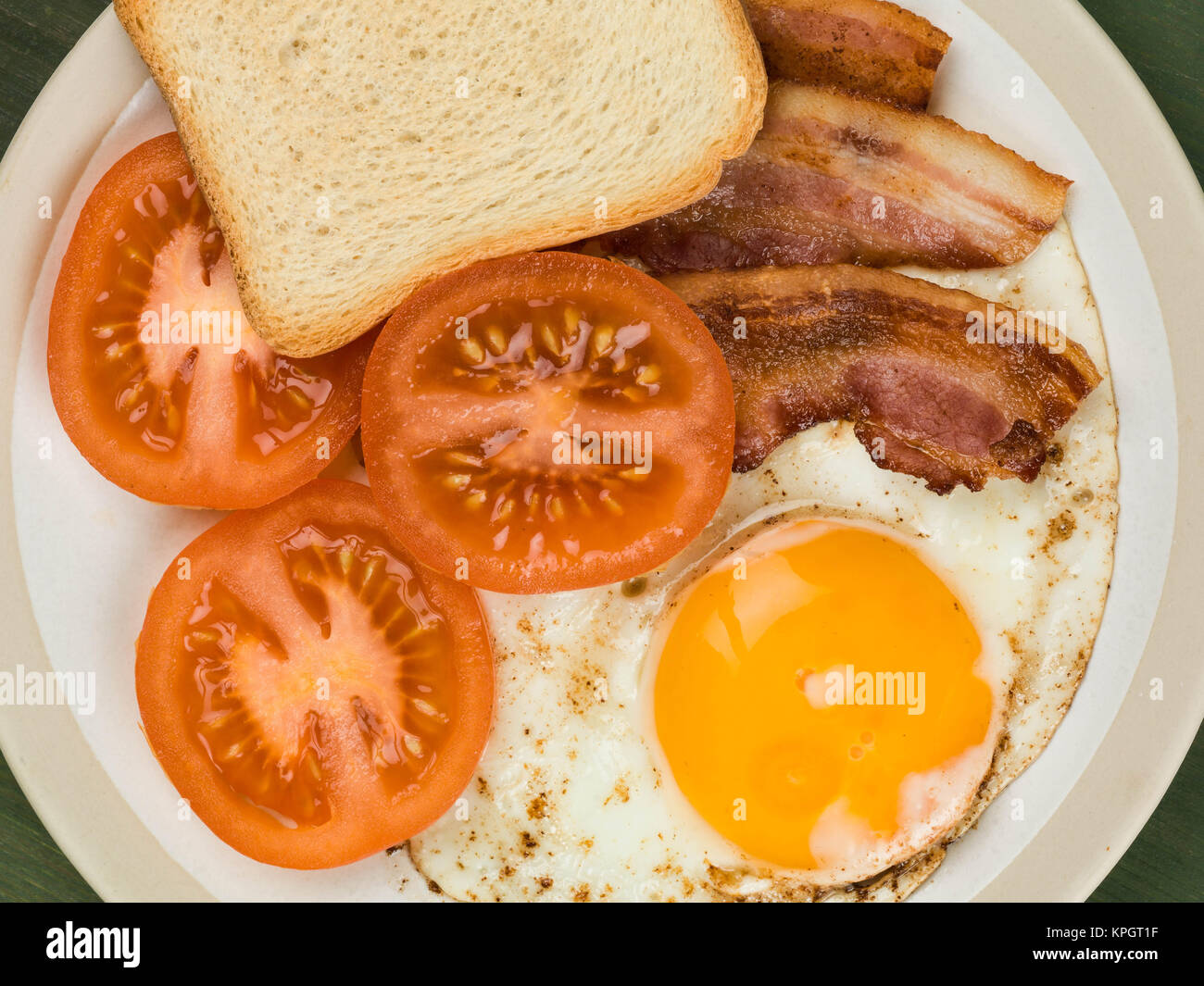 Bacon Egg and Tomato With French Toast Breakfast Food Against a Green Background Stock Photo