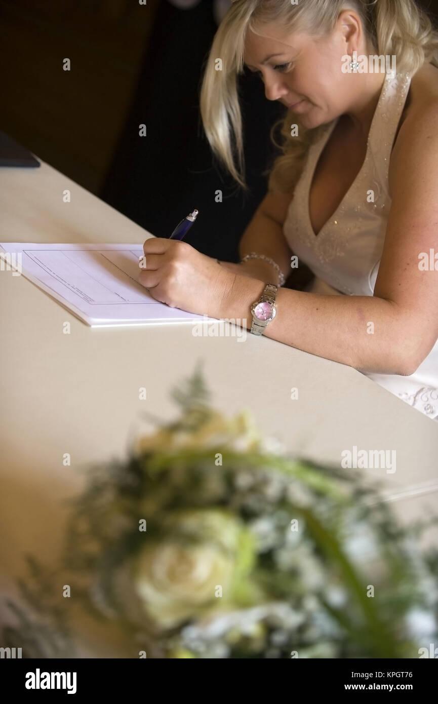 Model released , Standesamtliche Hochzeit, Braut unterschreibt Heiratsurkunde am Standesamt - married in a civil - Stock Image