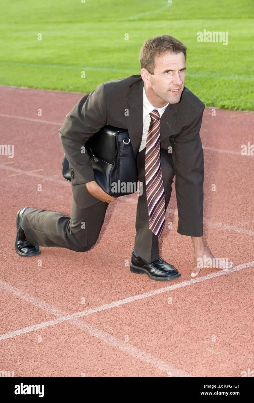 Model released , Gesch?ftsmann an der Startlinie auf einer Laufbahn, Symbolbild Berufliche Laufbahn - businessman - Stock Image
