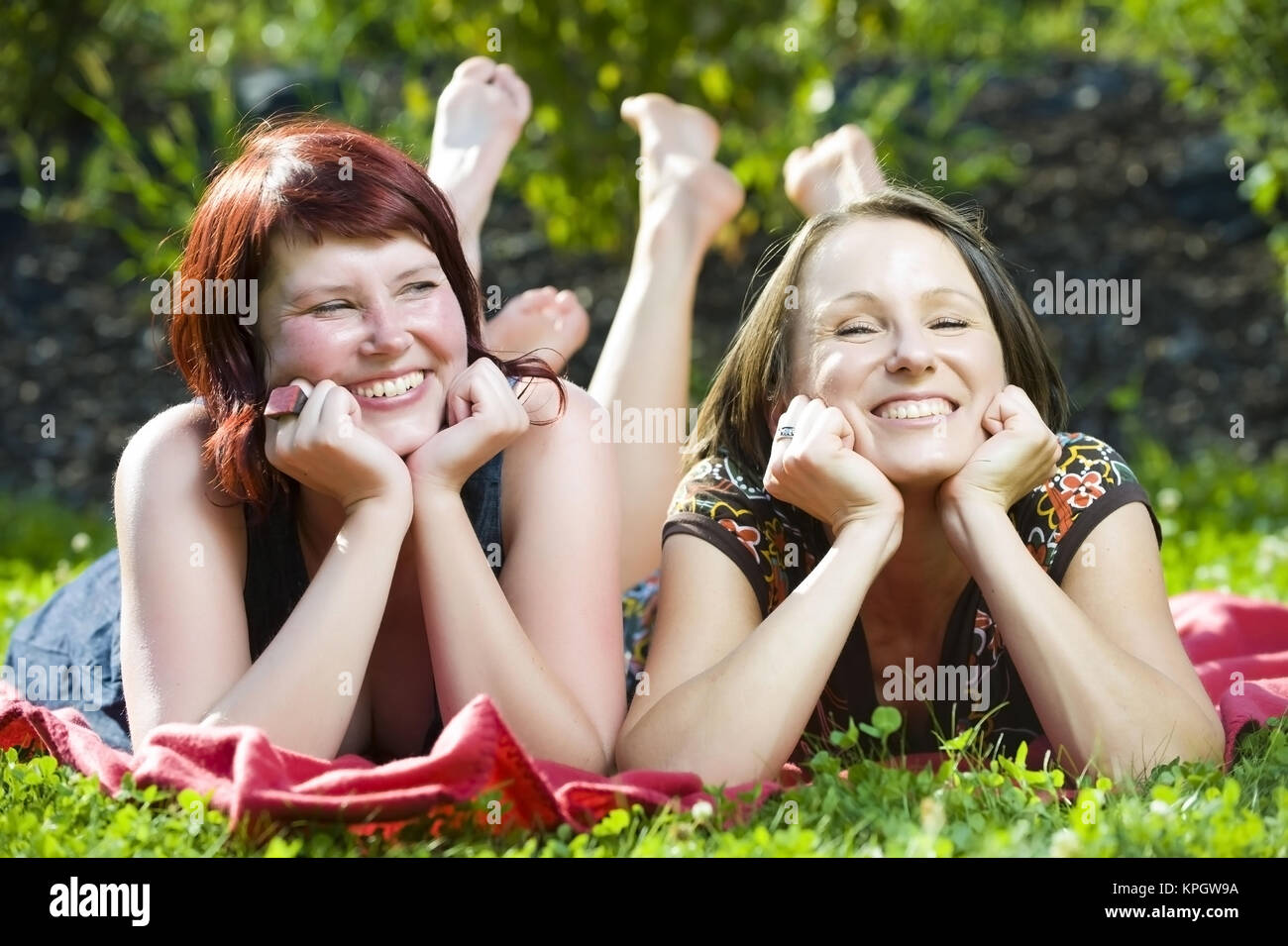 Model released , Zwei junge, froehliche Frauen liegen nebeneinander auf einer Decke in der Wiese - two young, lucky - Stock Image