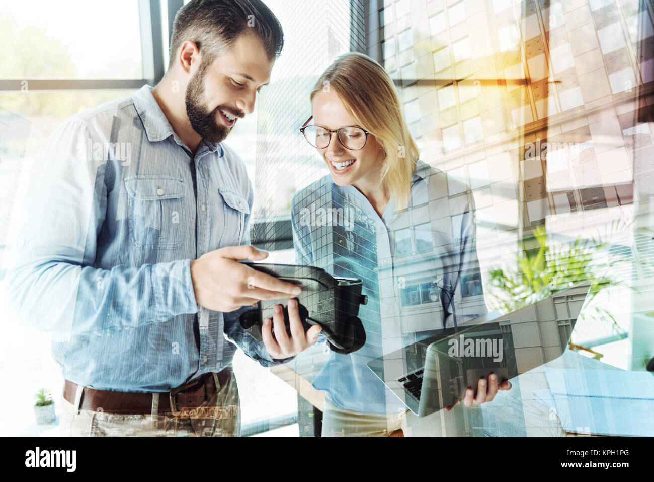 Joyful surprised employees keeping gadgets and observe it. - Stock Image