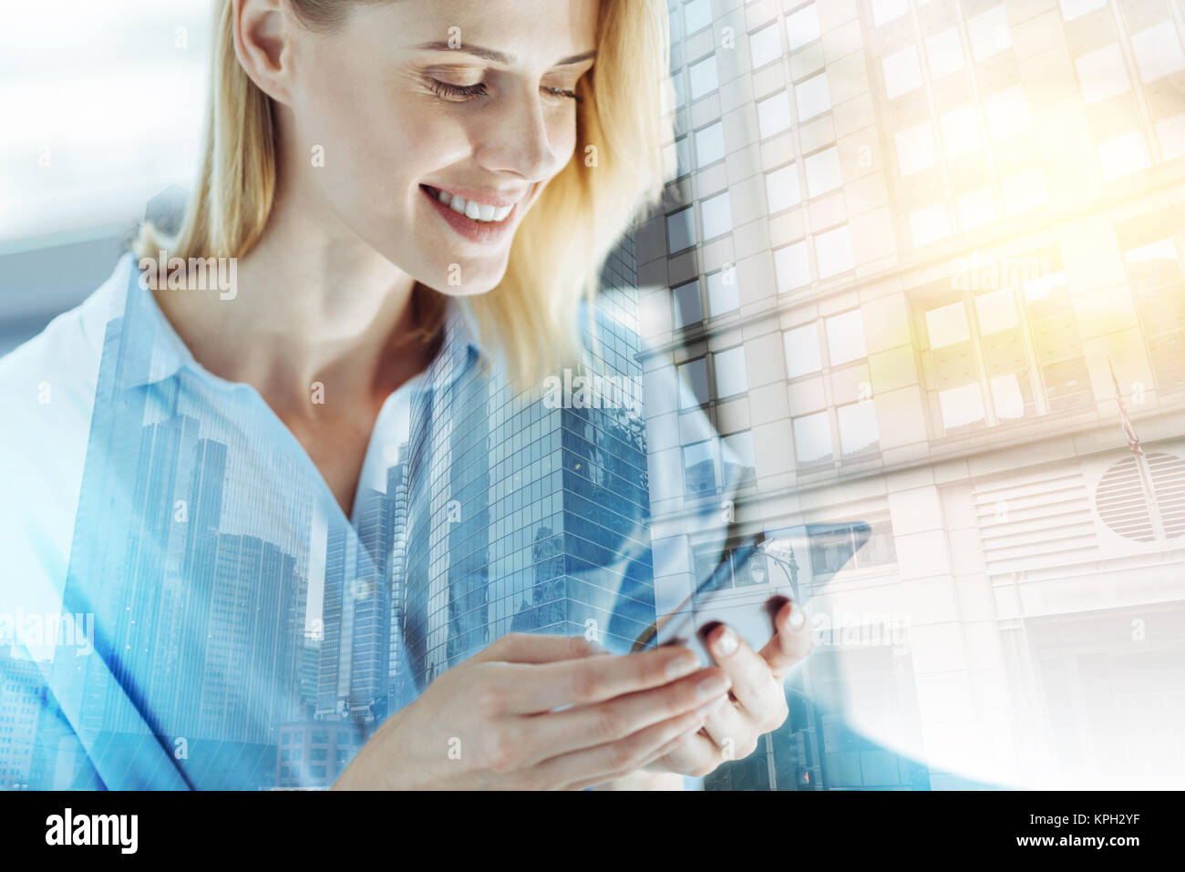 Pretty pleasant woman using cellphone and messaging. - Stock Image