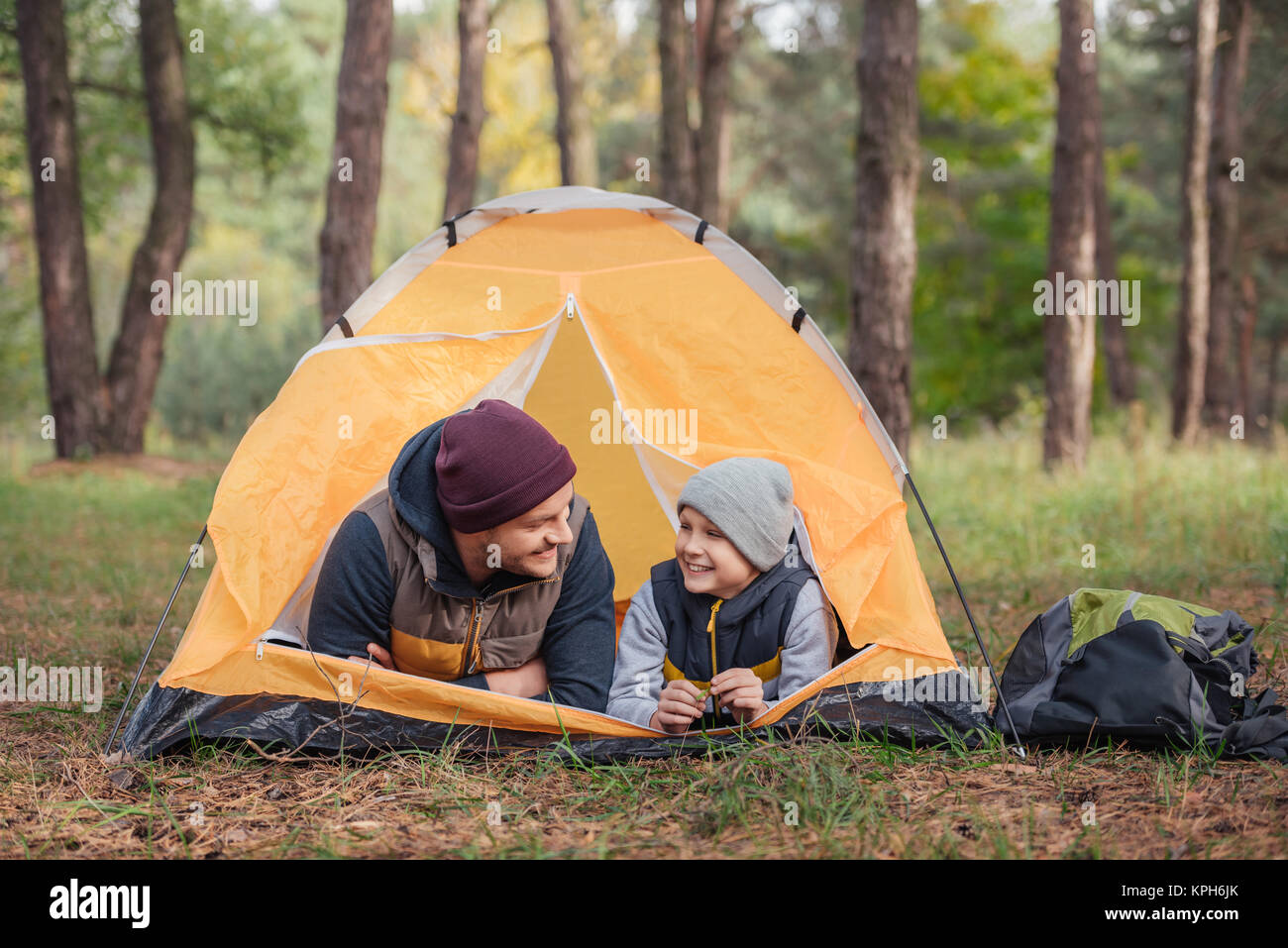 father and son lying in tent - Stock Image