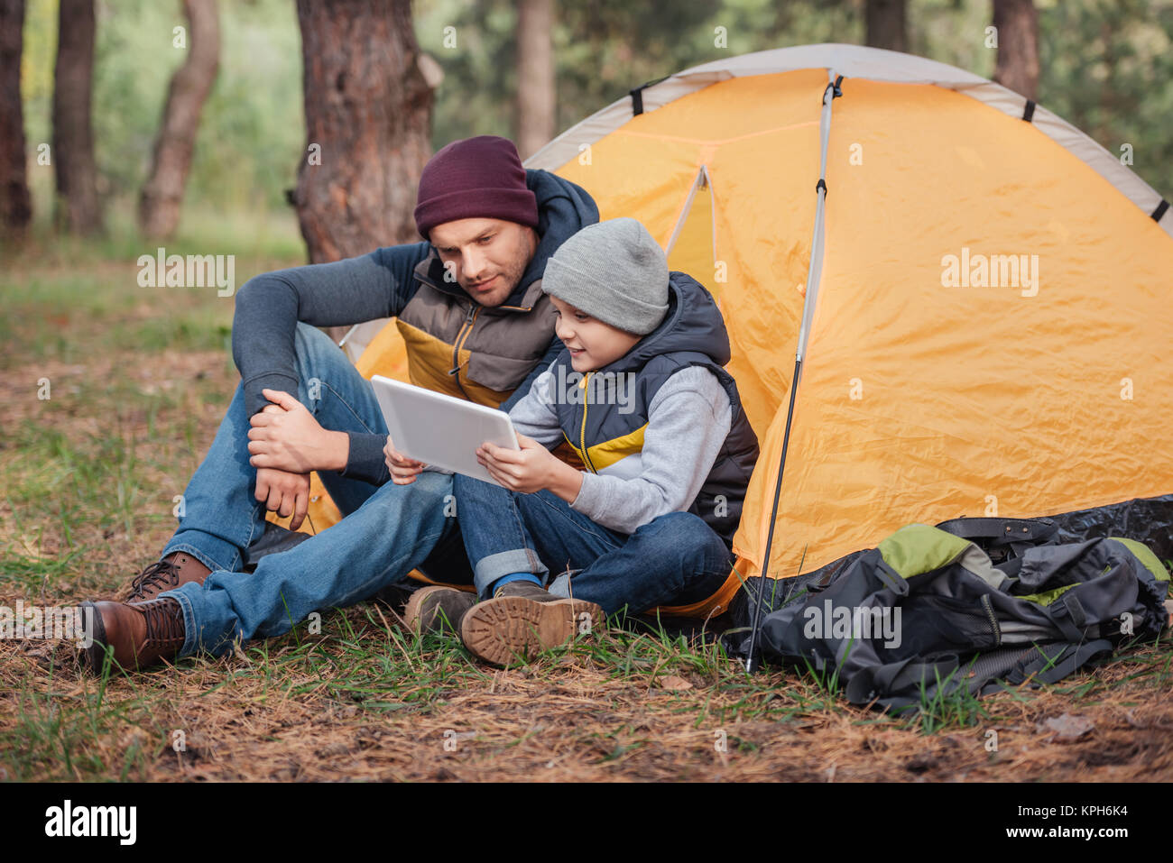father and son with digital tablet in forest - Stock Image