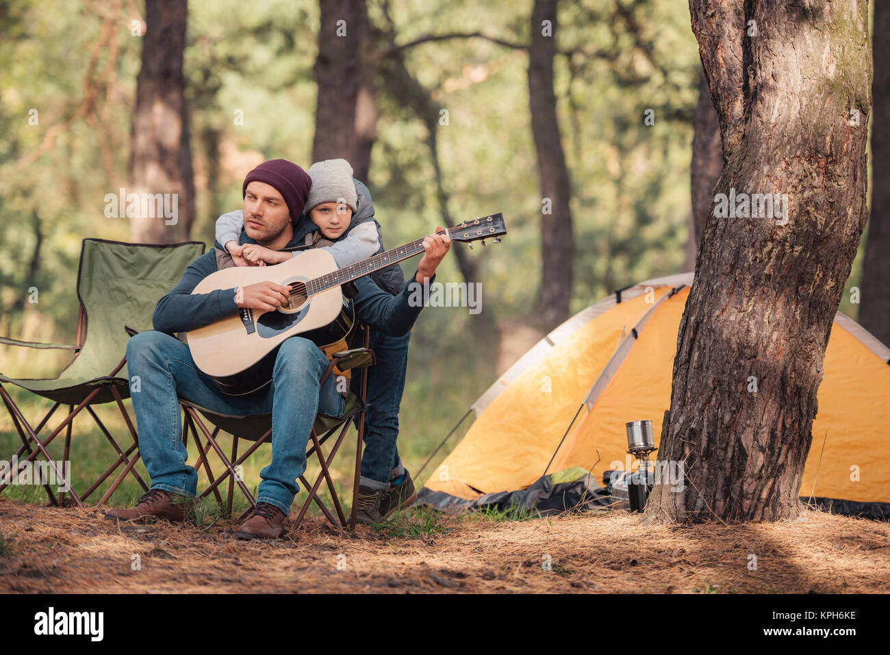 father and son with guitar in forest - Stock Image